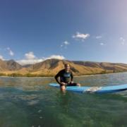 ManSitting on Board West Maui Mountain Background