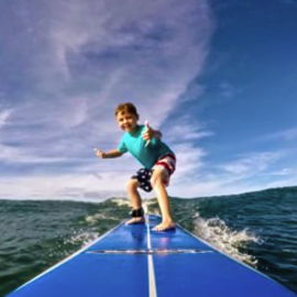 child learning to surf on maui