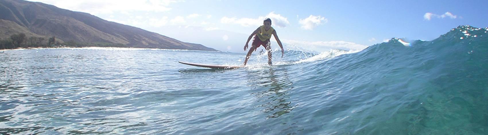 boy surfing with sun behind him