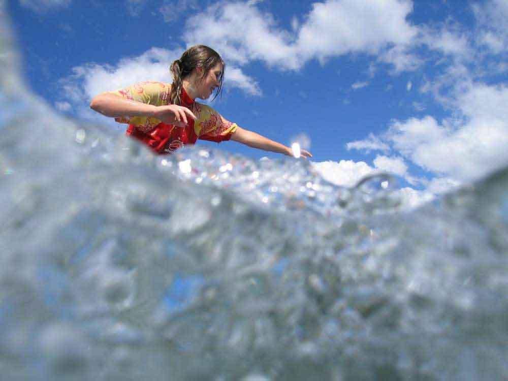 women surfing wave